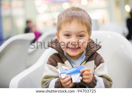 Cute little boy playing with a toy airplane in airport