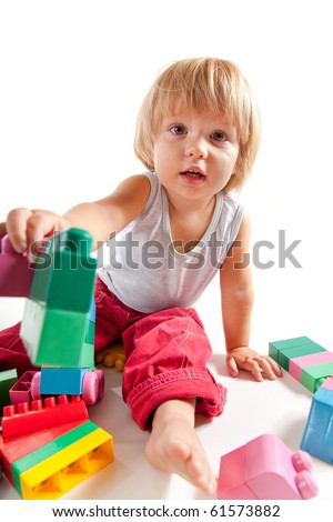 Cute little boy playing with blocks and stretching one in camera - stock photo