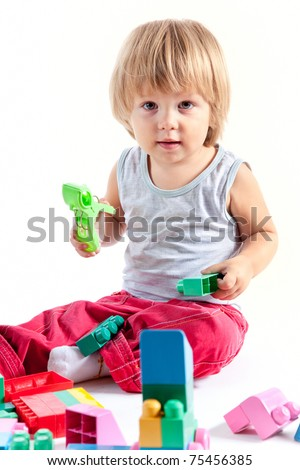 Cute little boy playing with blocks, isolated on white background - stock photo