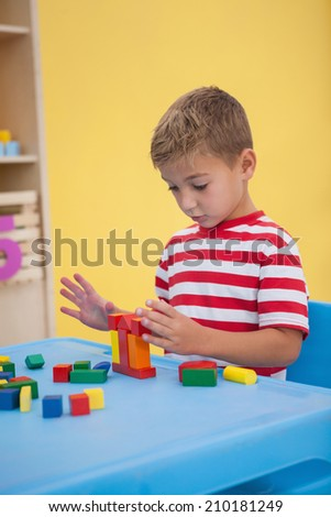 Cute little boy playing with building blocks at the nursery school
