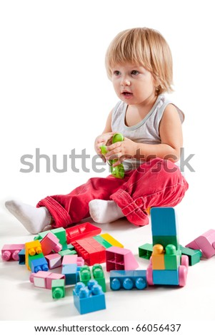 Cute little boy playing with colorful blocks, studio shot
