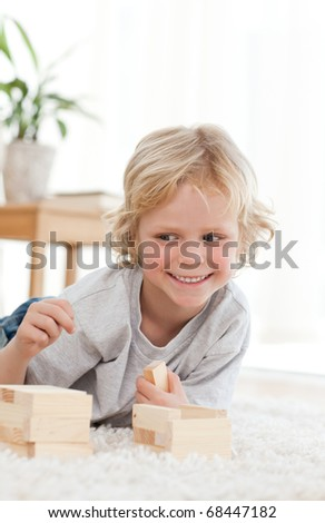 Cute little boy playing with dominoes lying on the floor of the living room - stock photo