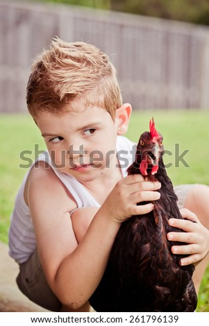 Cute little boy playing with his bet chicken. - stock photo