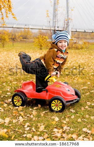 cute little boy playing with his car outdoor - stock photo