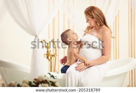 Cute little boy playing with his pregnant mom in bathroom at home - stock photo