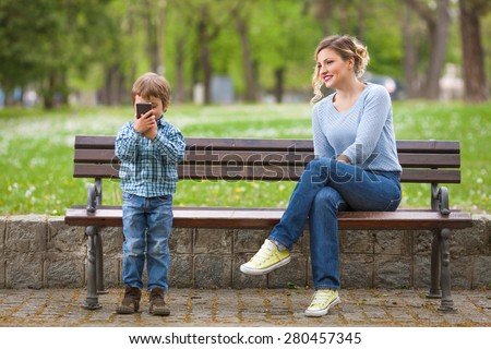 Cute little boy playing with mobile phone and his mother sitting on a park bench - stock photo