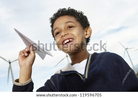 Cute little boy playing with paper plane at wind farm - stock photo