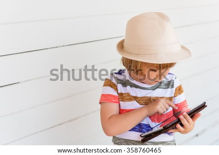 Cute little boy playing with tablet pc wearing a hat, standing against white wooden background - stock photo