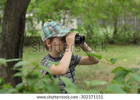 cute little boy playing with the binocular - stock photo