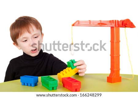 cute little boy playing with the toy lifting crane - stock photo