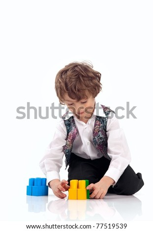Cute little boy playing with toy construction set over white background