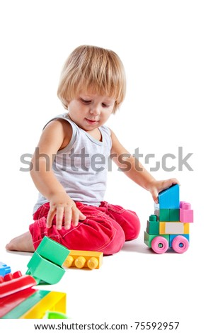 Cute little boy playing with toys, isolated on white background