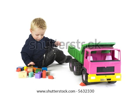 cute little boy plays with a big truck