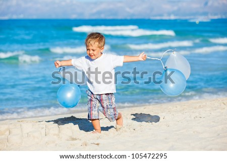 Cute little boy plays with ballons on the beach - stock photo