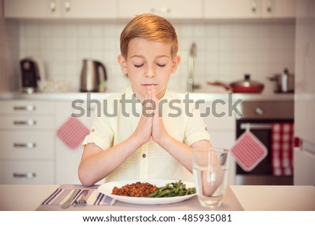 Cute little boy pray before eating meal at home