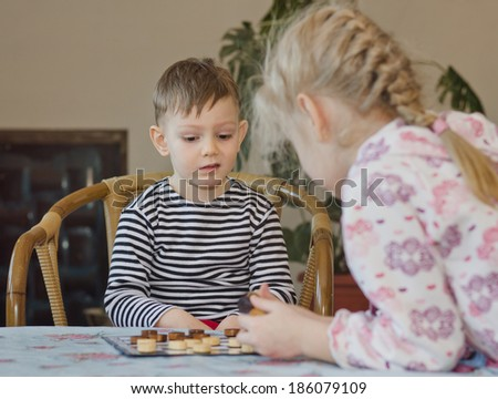 Cute little boy pulling a face and grimacing as he looks at the position of his pieces on a checkers board while playing a game with his sister - stock photo