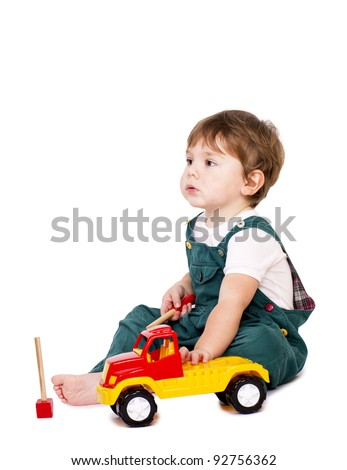 Cute little boy repairing and inspecting a plastic toy truck.
