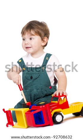Cute little boy repairing and inspecting some plastic toy trucks. - stock photo