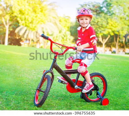 Cute little boy riding a bike in the park in bright sunny day, spending leisure time outdoors, enjoying summer sport, happy childhood concept