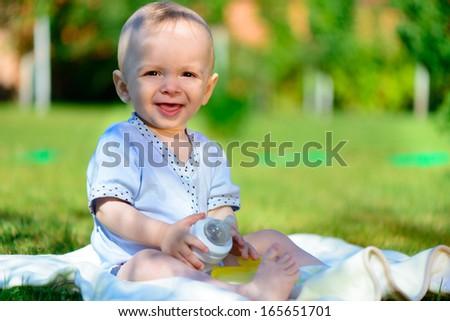 Cute little boy siting on green grass at summer park - stock photo