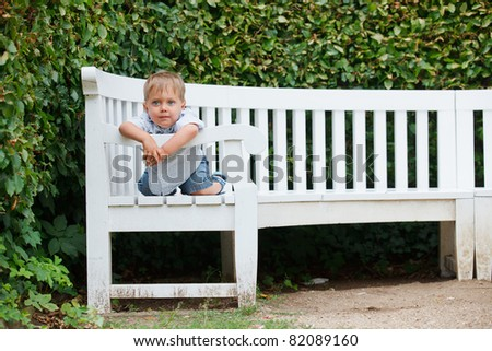 Cute little boy sits on a bench in a park - stock photo