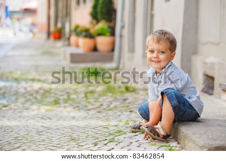 Cute little boy sits on the doorstep on a city street