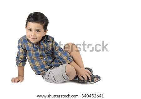 Cute little boy sitting isolated on white background. looking at camera