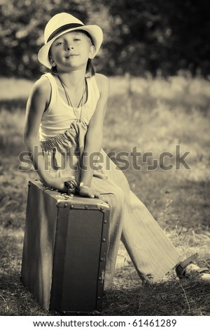 Cute little boy sitting on a big suitcase. Retro style. - stock photo