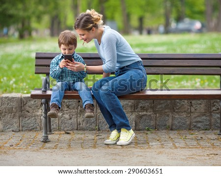 Cute little boy sitting on a park bench with his mother and playing with mobile phone