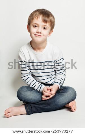 Cute little boy sitting on the floor - stock photo