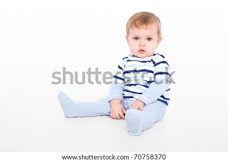 Cute little boy sitting on the floor - stock photo
