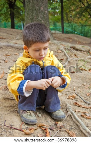 Cute little boy sitting on the ground and playing outdoor. - stock photo