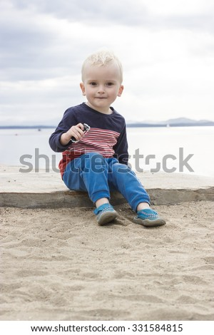 cute little boy sitting on the shore playing with a small toy car with water and mountains at the background