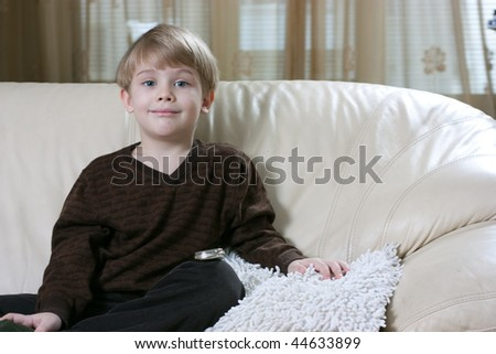 Cute little boy sitting on the sofa and smiling - stock photo