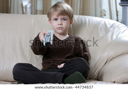 cute little boy sitting on the sofa and watching tv with a remote control - stock photo