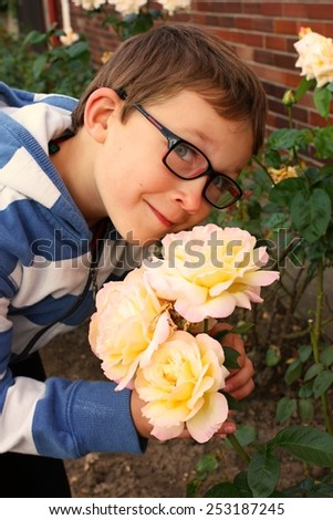 Cute little boy smelling the roses - stock photo