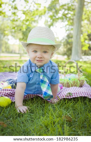 Cute Little Boy Smiles on Picnic Blanket With Easter Eggs Around Him. - stock photo
