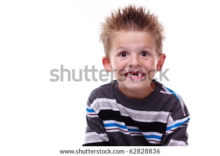 Cute little boy smiling and showing his missing teeth on a white background