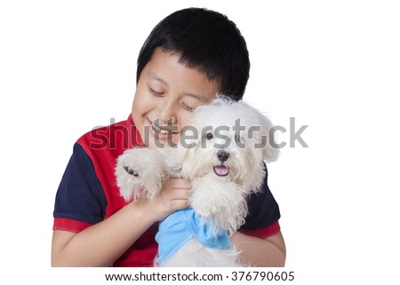 Cute little boy smiling happy in the studio while embracing a maltese dog, isolated on white background - stock photo