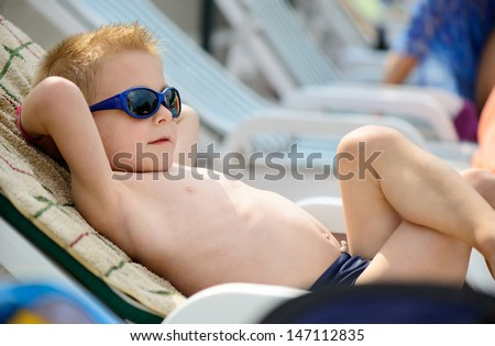Cute little boy sunbathing at ocean beach - stock photo