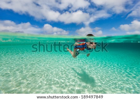 Cute little boy swimming underwater in tropical sea - stock photo