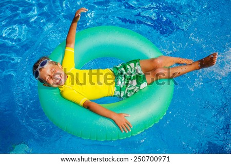 Cute little boy swims in a pool in an green life preserver - stock photo