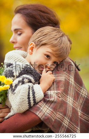 Cute little boy tired of walking in nature carried by his mother.  - stock photo