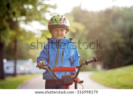Cute little boy, toddler child, riding bike in a helmet, back lit - stock photo