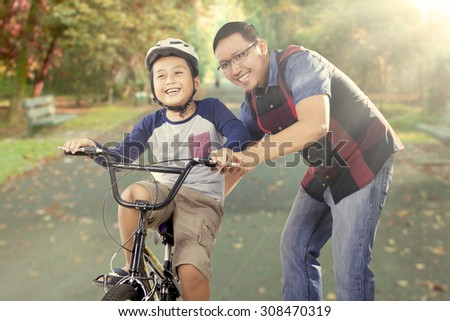 Cute little boy try to ride a bike with his father on the road at the park, shot outdoors - stock photo