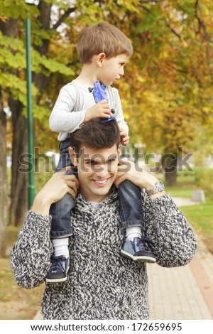 Cute little boy walking with his dad in park. - stock photo