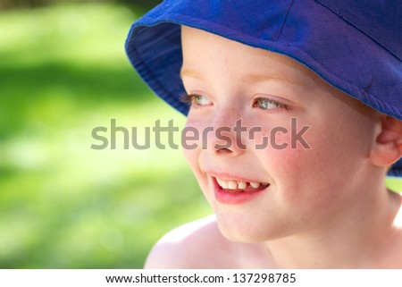 cute little boy wearing a sun hat in the garden smiling with joy - stock photo