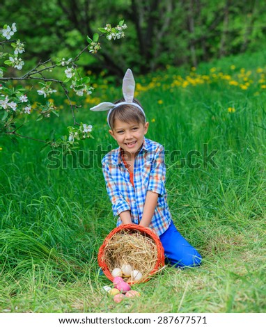 Cute little boy wearing bunny ears playing with Easter eggs in blossoming apple garden on spring day - stock photo
