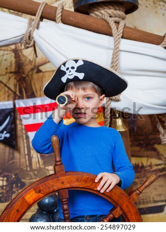 Cute little boy wearing pirate costume on the deck of a ship - stock photo