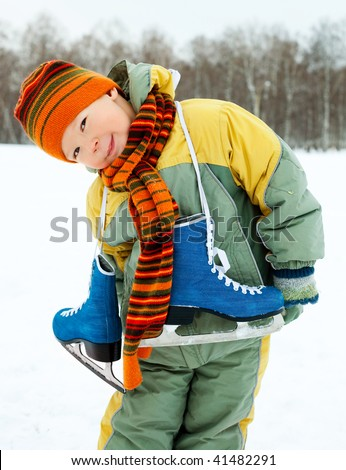 cute little boy wearing warm winter clothes going ice skating - stock photo